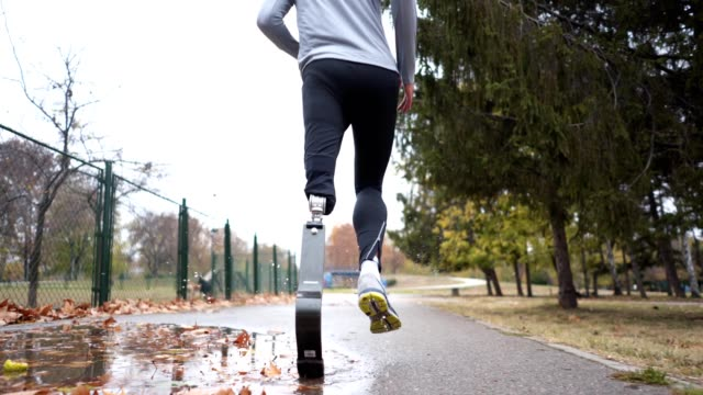 Adaptive athlete running outdoors in autumn Young and athletic man with a artificial leg, exercising outdoors, living a healthy lifestyle recovering. artificial limb stock videos & royalty-free footage