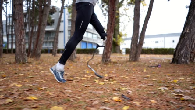 Adaptive athlete running outdoors Young and athletic man with a artificial leg, exercising outdoors, living a healthy lifestyle recovering. artificial limb stock videos & royalty-free footage