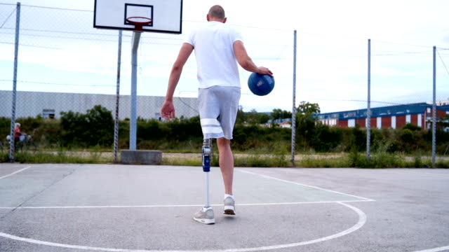 Adaptive athlete taking a shot at basketball court A man with prosthetic leg, walking a dog, playing tenis and basketball prosthetic equipment stock videos & royalty-free footage