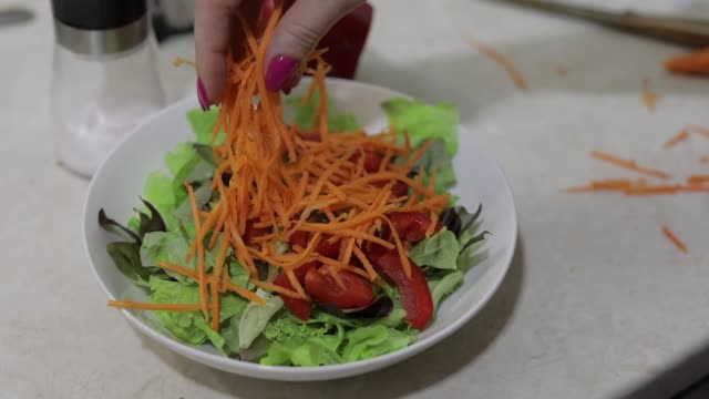 vídeos de stock e filmes b-roll de add chopped carrots in salad with red pepper and lettuce salad - red bell pepper isolated