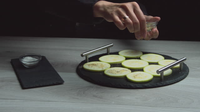 add seasoning to zucchini, women's hands close up, table shooting from above