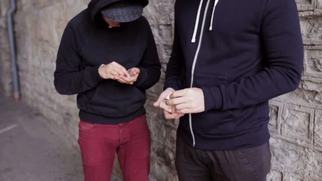 stockvideo's en b-roll-footage met verslaafde kopen dosis van drugsdealer op straat - amfetamine