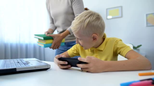 stockvideo's en b-roll-footage met verslaafd jongen spelen mobiele telefoon spel in plaats van het doen huiswerk, moeder scolding zoon - kids online abuse