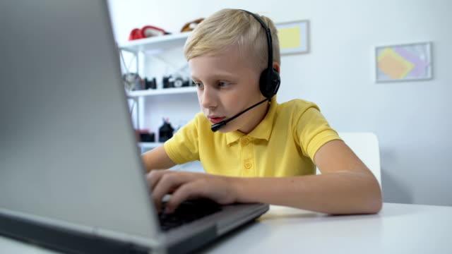 stockvideo's en b-roll-footage met verslaafde mannelijke kid in headset spelen spel op laptop computer moderne technologieën - kids online abuse
