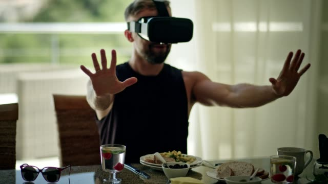 vídeos de stock e filmes b-roll de addicted to technology. man having breakfast with vr - ignorância