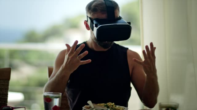 Addicted to technology. Man having breakfast with VR