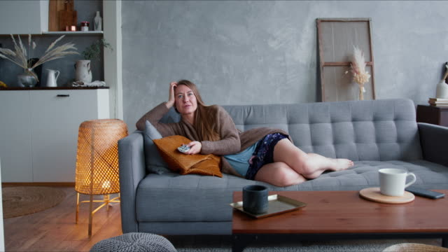 tv addiction on quarantine. young happy attractive caucasian blonde woman watching serial at home on comfortable sofa. - divano procrastinazione video stock e b–roll