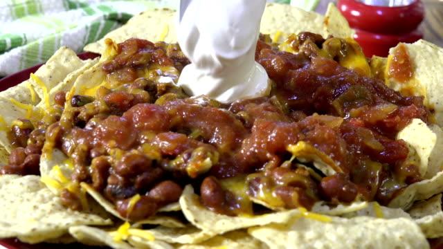 nachos mit einen klecks sauerrahm hinzufügen - chilli stock-videos und b-roll-filmmaterial