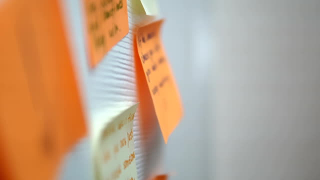 vídeos de stock e filmes b-roll de adding a message sticker on board. closeup of creative business team brainstorming ideas and concepts - papel adesivo