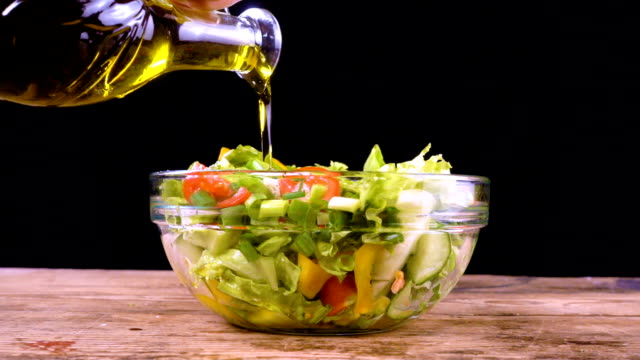 adding a olive oil to salad in glass bowl video