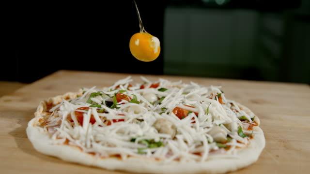 SLO MO ajoutant un oeuf cru sur la pizza - Vidéo