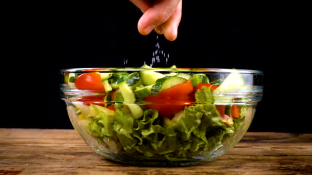 adding a salt to salad in glass bowl adding a salt to salad in glass bowl, cooking for healthy nutrition, slow motion 250 fps salad bowl stock videos & royalty-free footage