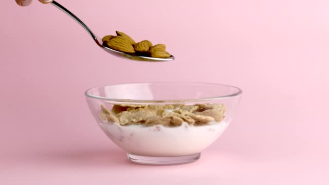 Adding almond on top of cereal for healthy vegan diet breakfast