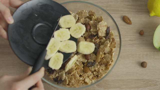 Adding bananas to Muesli for breakfast