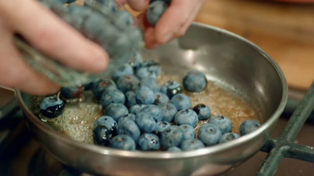 vídeos de stock e filmes b-roll de adding blueberries into a pan with melted butter and brown sugar - vacínio