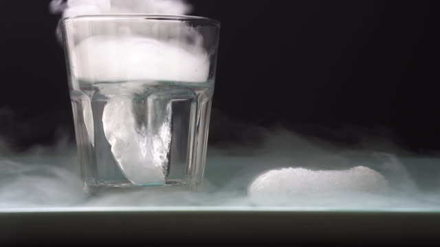 Adding dry ice to a glass of water Adding frozen carbondioxide, dry ice, to a glass of water. Fog bubbles up as the air freezes from the cold gas. Carbondioxide sublimates directly from solid to gas. Please use protection when handling dry ice. solid stock videos & royalty-free footage