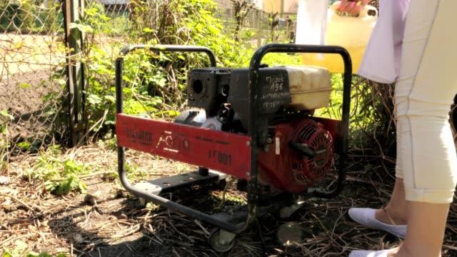 vídeos y material grabado en eventos de stock de añadir gasolina para el generador - generadores