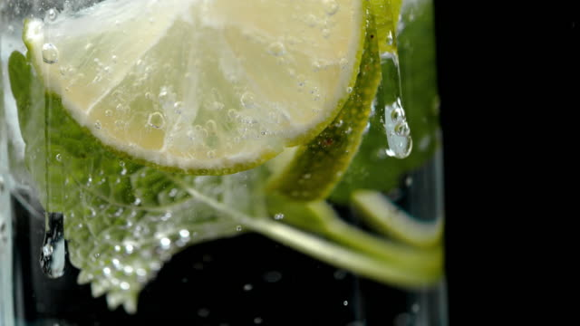 SLO MO Adding ice to a lime drink