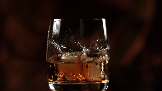slo mo adding ice to a whiskey - whisky video stock e b–roll