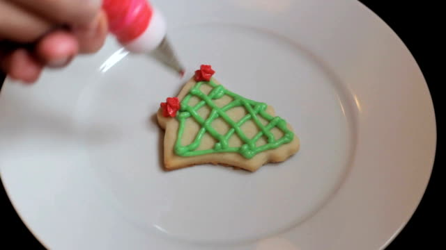 Adding Red Icing To Bell Shaped Christmas Cookie video