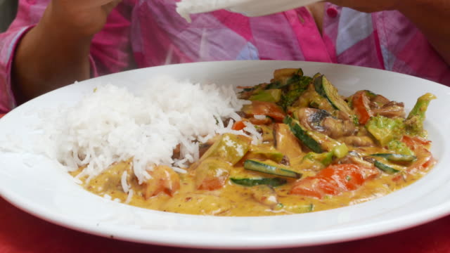 Adição de arroz com legumes ao curry - vídeo