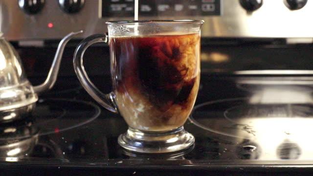 vídeos de stock e filmes b-roll de adding rich cream into coffee - café gelado