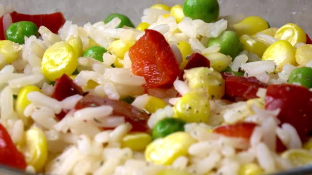vidéos et rushes de ajout d'assaisonnement pour riz et salade de légumes, bouchent vidéo fullhd - couleur saturée