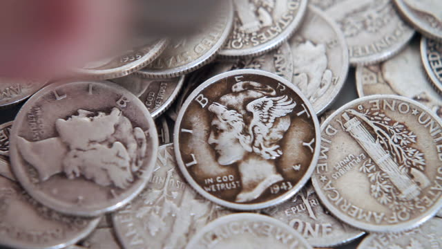 Adding to the pile of silver coins  silver metal stock videos & royalty-free footage