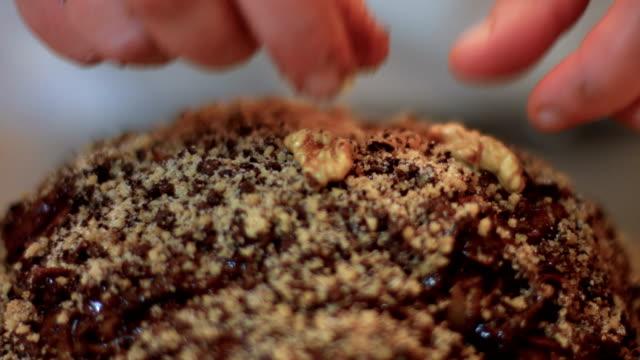 vídeos de stock e filmes b-roll de adding walnuts to a traditional cake - christmas cake