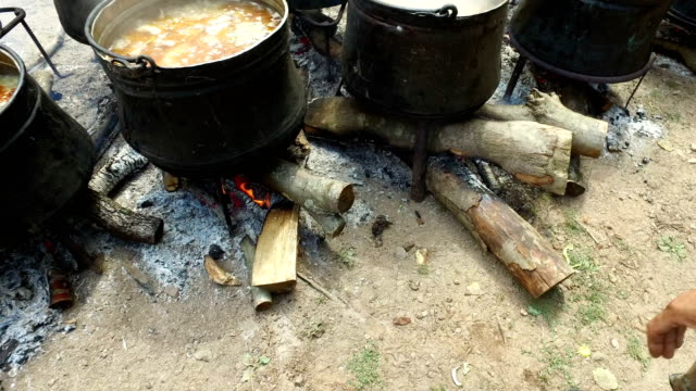 Adding wood limber to campfire, cooking food in a large cauldron on the fire video