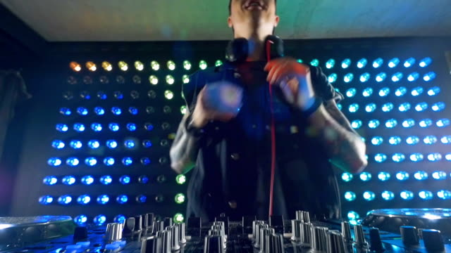 A DJ adds some bass on his mixer. video