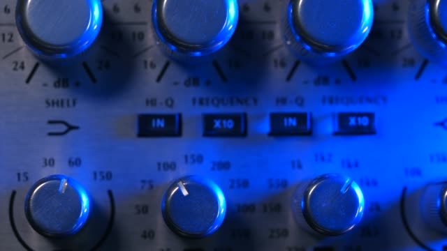 adjustable handles on the compressor panel in professional recording studio. blue neon light. sound mixing concept. dolly shot. 4k - disco audio analogico video stock e b–roll