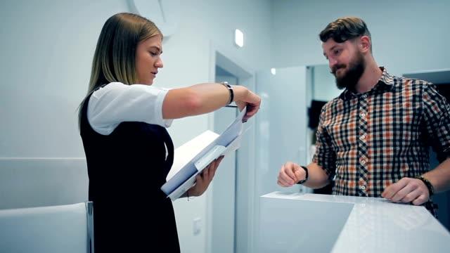 vídeos y material grabado en eventos de stock de administrador transmite cuestionario al cliente - recepcionista