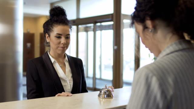 yönetici bir otelde bir iş kadını bir odadan bir anahtar verir - hotel reception stok videoları ve detay görüntü çekimi