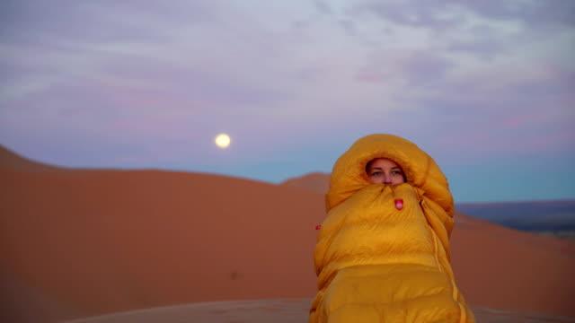 admiring desert sunset. cold evening. full moon. - arancione video stock e b–roll