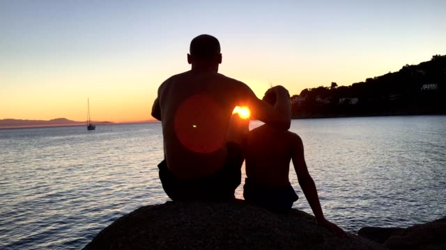 Admiring sunset. Father and son sitting on a rocky beach looking at view - video