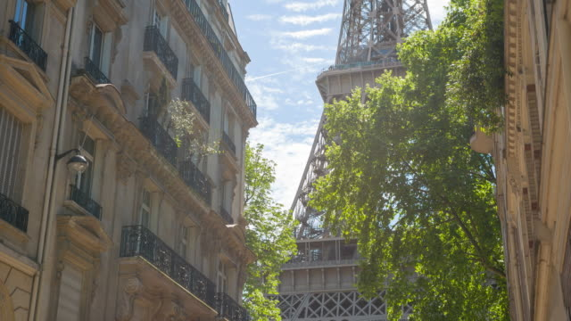 admiring the majestic eiffel tower from inbetween parisian buildings - francja filmów i materiałów b-roll