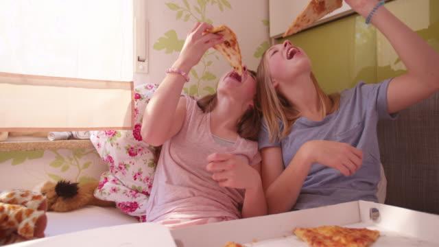 teenager-mädchen essen große köstlicher pizza im bett - teenage friends sharing food stock-videos und b-roll-filmmaterial