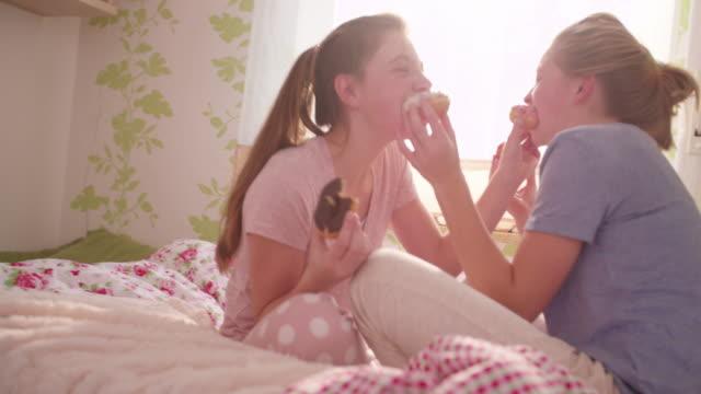 思春期の少女フィーディング eachother ドーナッツ」で、カラフルなベッドルーム - 高等学校点の映像素材/bロール