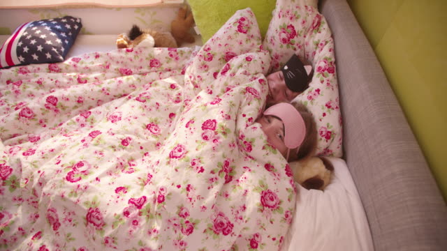 Adolescent girls hiding under the bed covers with sleeping masks video