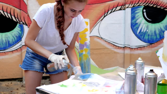 adolescent with aerosol paint at background of graffiti in slow motion, street painting, girl with spray paint in hand