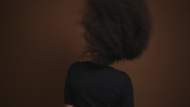stockvideo's en b-roll-footage met schattig african american girl schudden haar hoofd geïsoleerd op bruine achtergrond - afro amerikaanse etniciteit