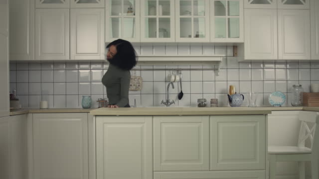Adorable african american woman dancing in the kitchen at home