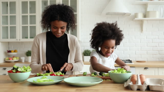 Adorable african daughter helping mum cutting vegetable salad in kitchen