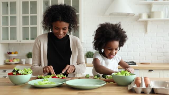 vídeos de stock, filmes e b-roll de adorável filha africana ajudando mãe cortando salada vegetal na cozinha - alimentação saudável