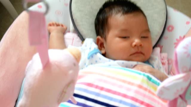vídeos de stock, filmes e b-roll de adorável bebê asiático sente sono, deitado em um berço de balanço - mobile