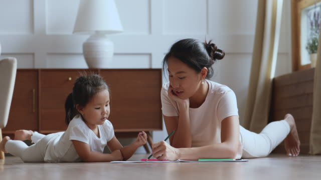 Adorable asian little baby girl drawing with happy young mother.