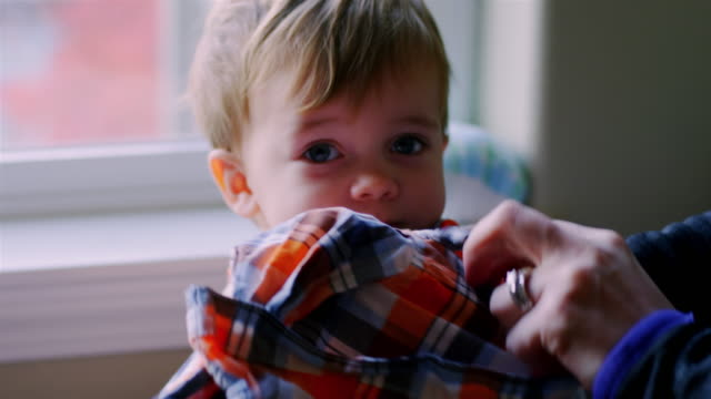 Adorable baby boy being dressed in his room video