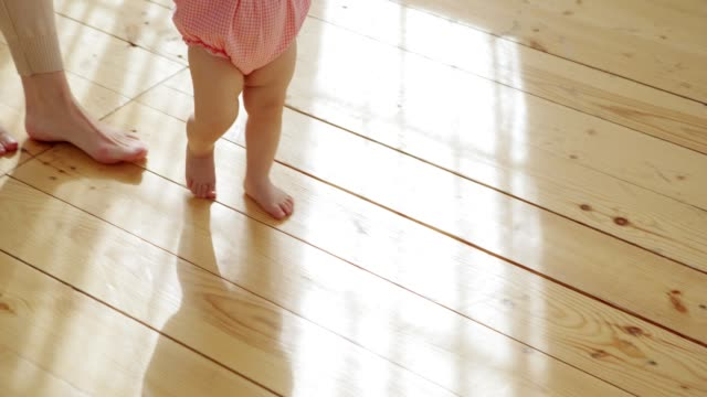 Adorable baby girl learning to walk on hardwood floor at home supported by her loving mother, tracking shot Adorable baby girl learning to walk on hardwood floor at home supported by her loving mother, tracking shot first occurrence stock videos & royalty-free footage