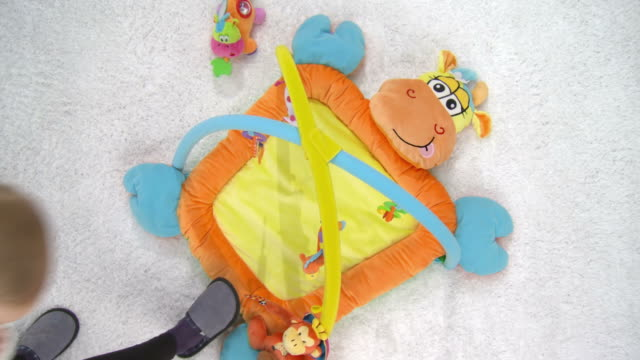 HD CRANE: Adorable Baby In Playmate HD1080p: CRANE shot of a young mother lay down her adorable baby on a colorful playmate. All visible toys are official property released playroom stock videos & royalty-free footage